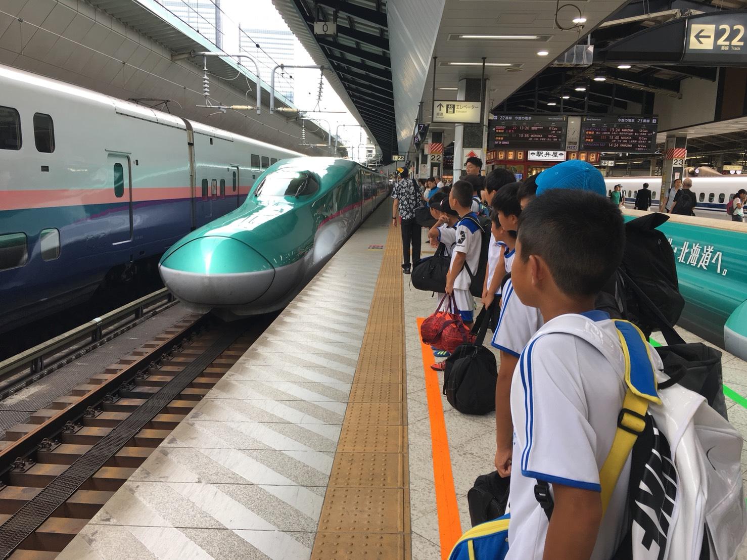 ホームで新幹線を待つ選手たち